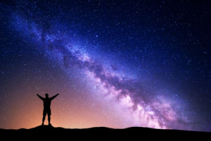 photo of night sky with man silhouetted against it