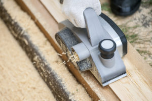 photo of hands and tool working on wood