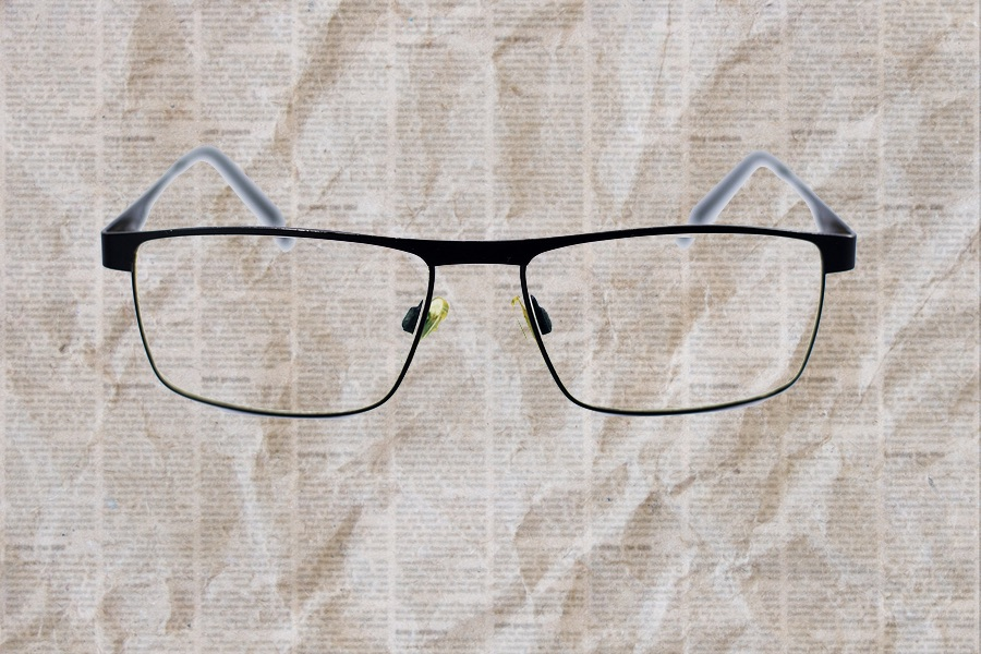 photo of reading glasses on top of crumpled unreadable newsprint