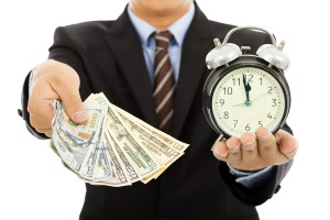 Photo of businessman holding money and clock