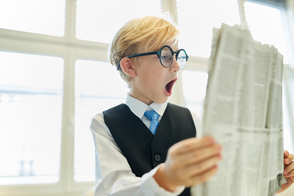 photo of child reading newspaper