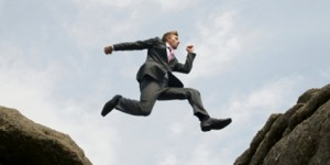 photo of businessman jumping a chasm between two rocks