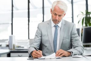 Serious executive in suit reviewing a white paper - That White Paper Guy