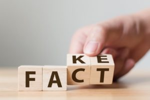 photo of hand turning over wooden block letters to change FAKE into FACT