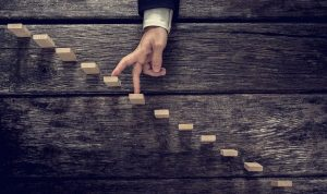 Retro image of a businessman walking his fingers up wooden steps mounted in rustic wooden boards towards light in a conceptual image of personal development growth and success.