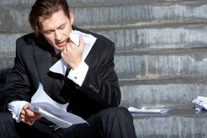 photo of frustrated business man trying to read a poor white paper