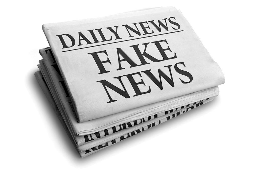 newspaper with headline saying Fake News
