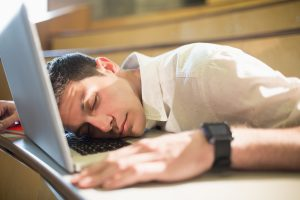Photo of young business person falling asleep during boring slideshow