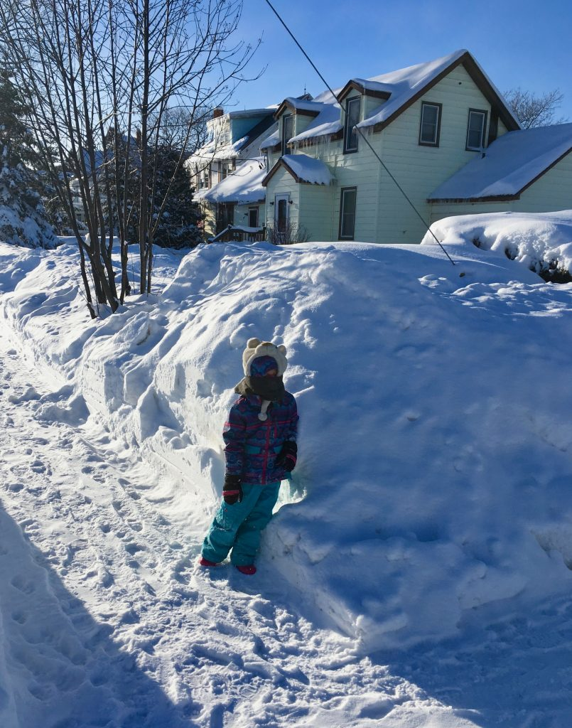 photo of child beside snowbank