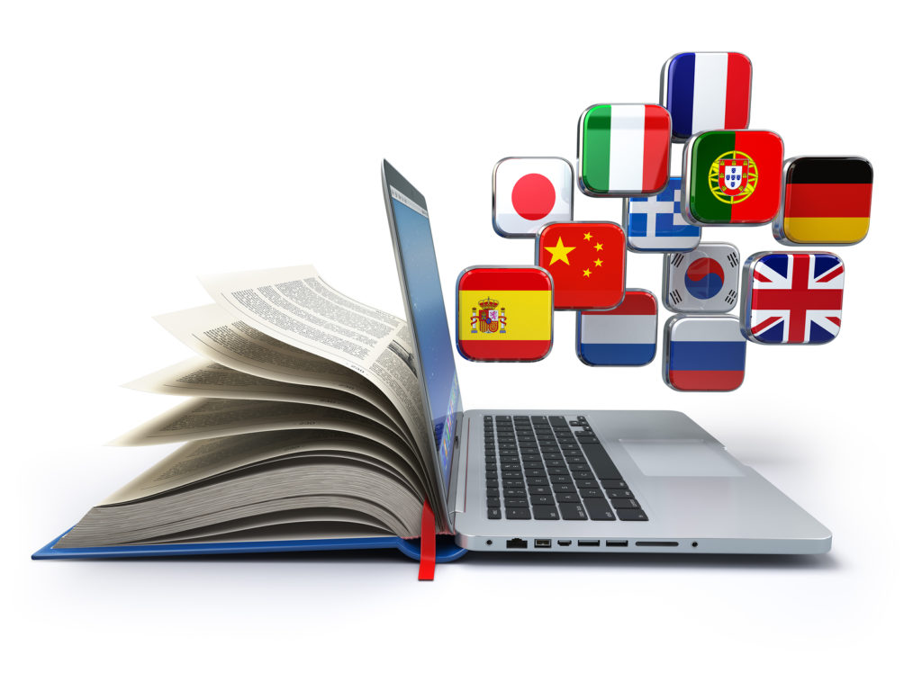 book and laptop with many flags to symbolize translation