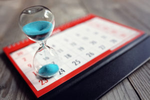 Photo of hourglass on calendar to show meeting a deadline for a white paper