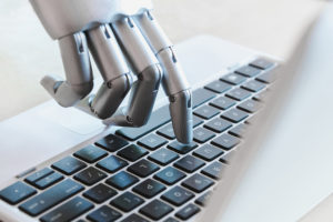 Robot fingers point to laptop button