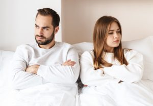 husband and wife disagreement in bed over their white paper