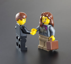 Lego figures shaking hands to represent a white paper with both editorial + business success