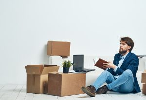a man sitting mnong moving boxes