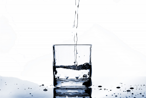 clear stream of water poured into a drinking glass