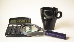 magnifying glass, calculator and coffee cup to symbolize revising a draft white paper