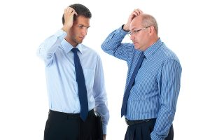 younger and older business men scratching their heads