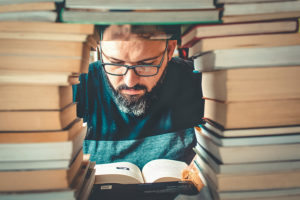 man seen through hole in pile of books