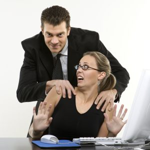 photo of young man with hands on shoulders of young man at office who doesn't like it