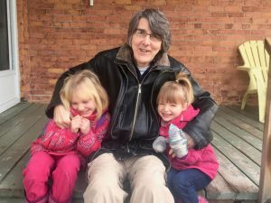 Photo of Gordon Graham on porch with two daughters